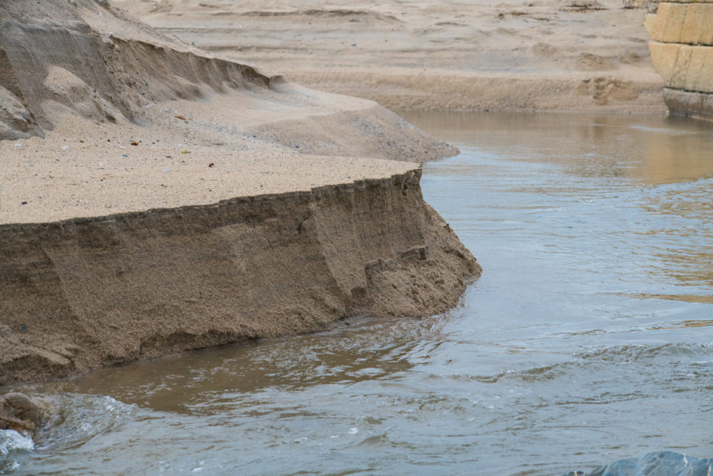 A sandbank on a beach in Cornwall being eroded by the tide